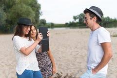 Adultos jovenes que toman imágenes y Selfies en Sandy Beach Foto de archivo