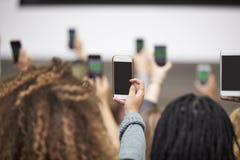 Adultos jovenes que toman las fotos con los teléfonos, cierre trasero de la visión para arriba Imagen de archivo libre de regalías