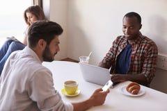 Adultos jovenes usando tecnología móvil en una cafetería Imagen de archivo