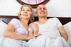 Adultos maduros que mienten en cama de la familia Foto de archivo libre de regalías