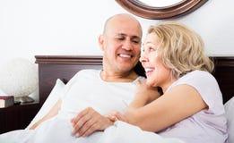 Adultos maduros que mienten en cama de la familia Imagen de archivo