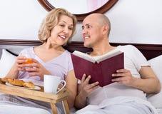 Adultos maduros que presentan con el desayuno y el libro Fotografía de archivo libre de regalías