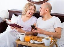 Adultos maduros sonrientes del positivo alegre que presentan con el desayuno Foto de archivo libre de regalías