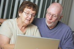 Adultos mayores en el ordenador portátil Imágenes de archivo libres de regalías