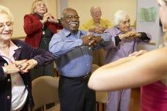 Adultos mayores en una clase que estira Fotografía de archivo