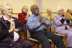 Adultos mayores en una clase que estira Imágenes de archivo libres de regalías