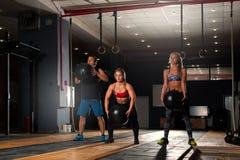 Adultos musculares jovenes que hacen posiciones en cuclillas con la bola pesada Fotografía de archivo