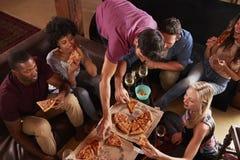 Adultos novos que comem pizzas em um partido em casa, vista elevado imagem de stock