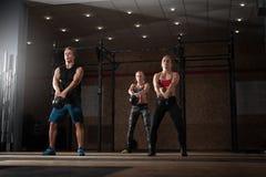 Adultos novos que fazem exercícios com sinos da chaleira Imagem de Stock Royalty Free