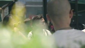 Adultos novos que recolhem discutindo a música em um lugar exterior do café vídeos de arquivo