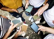 Adultos novos que usam smartphones em uns meios do círculo e em uma conexão sociais fotografia de stock royalty free
