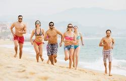 Adultos positivos que corren en la playa arenosa Fotos de archivo libres de regalías
