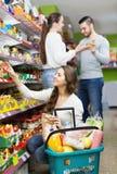 Adultos positivos que eligen la comida enlatada Imagen de archivo