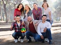 Adultos positivos que persiguen la bola al aire libre Fotografía de archivo libre de regalías