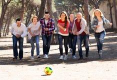 Adultos positivos que persiguen la bola al aire libre Foto de archivo libre de regalías