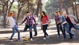 Adultos positivos que persiguen la bola al aire libre Fotos de archivo libres de regalías