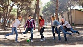 Adultos positivos que persiguen la bola al aire libre Foto de archivo