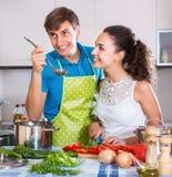 Adultos positivos que preparan la comida de los veggies Foto de archivo libre de regalías