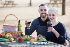 Adultos que beben el vino en la tabla Imagen de archivo libre de regalías