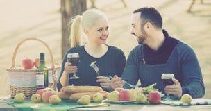 Adultos que beben el vino en la tabla Imágenes de archivo libres de regalías