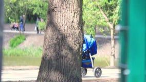 Adultos que caminan en la calle con los cochecitos de niño metrajes