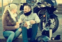 Adultos que charlan cerca de la motocicleta Imagen de archivo libre de regalías