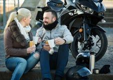 Adultos que charlan cerca de la motocicleta Fotografía de archivo libre de regalías