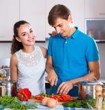 Adultos que colocan la tabla de cocina cercana con las verduras Fotografía de archivo libre de regalías