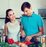 Adultos que colocan la tabla de cocina cercana con las verduras Imagen de archivo libre de regalías