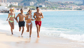 Adultos que corren en la playa arenosa Imagenes de archivo