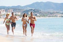 Adultos que corren en la playa arenosa Imagen de archivo