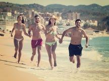 Adultos que corren en la playa arenosa Fotos de archivo libres de regalías