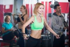Adultos que entrenan en gimnasio junto Imagen de archivo libre de regalías