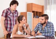 Adultos que firman documentos financieros Imagen de archivo