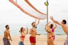 Adultos que juegan la bola en la playa del centro turístico Foto de archivo libre de regalías
