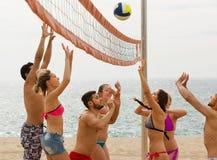 Adultos que lanzan la bola sobre red y la risa Fotos de archivo