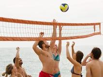 Adultos que lanzan la bola sobre red y la risa Foto de archivo libre de regalías