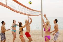 Adultos que lanzan la bola sobre red y la risa Fotos de archivo libres de regalías