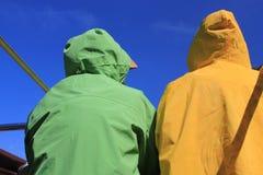 Adultos que llevan los impermeables brillantemente coloreados Imagen de archivo libre de regalías