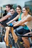 Adultos que montan las bicicletas inmóviles Imagen de archivo libre de regalías