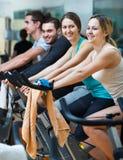 Adultos que montan las bicicletas inmóviles Imágenes de archivo libres de regalías