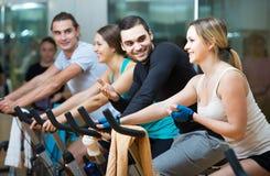 Adultos que montan las bicicletas inmóviles en club de fitness Foto de archivo