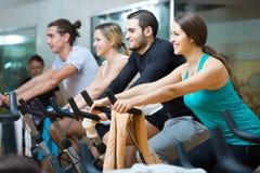 Adultos que montan las bicicletas inmóviles en club de fitness Fotografía de archivo libre de regalías