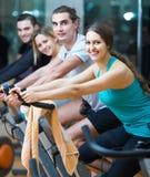 Adultos que montan las bicicletas inmóviles en club de fitness Fotos de archivo