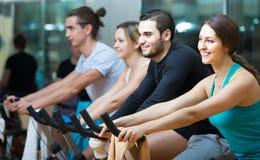 Adultos que montan las bicicletas inmóviles en club de fitness Foto de archivo libre de regalías
