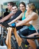 Adultos que montan las bicicletas inmóviles en club de fitness Imágenes de archivo libres de regalías