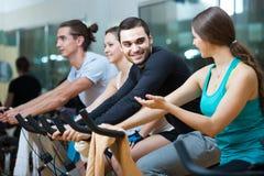 Adultos que montan las bicicletas inmóviles en club de fitness Imagenes de archivo
