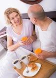 Adultos que presentan con café y pasteles Imagen de archivo libre de regalías