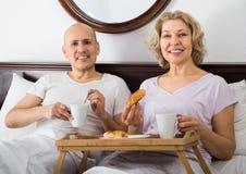 Adultos que presentan con café y pasteles Fotografía de archivo