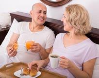 Adultos que presentan con café y pasteles Fotografía de archivo libre de regalías